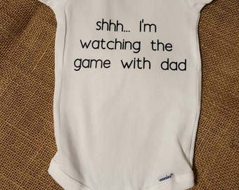 Customized Onesie.  Shhh... I'm watching the game with dad.