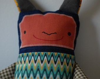 Colorfull animal soft toy with pointed ears. Zigzag, tile and flower patterns. Made by Roucoucou in Quebec by hand.