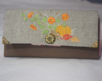 Long form of faux leather and linen/cotton embroidered purse