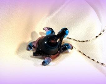 A dark blue sparkly swirl turtle necklace