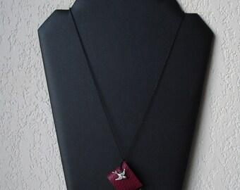 Collier livre miniature en cuir bordeaux épaix et petite hirondelle argentée