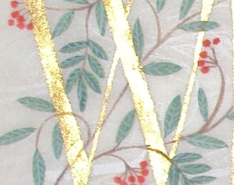Initial letter W in gold with Rowan and Laurel leaves on silk paper