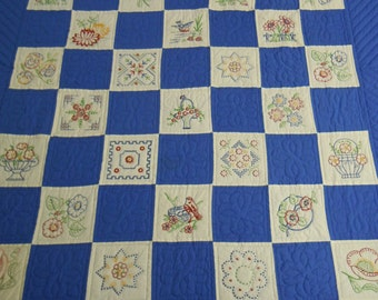 """Quilt: Hand embroidered block quilt featuring 32 embroidered blocks alternating w. solid blue fabric  hand quilted 86"""" x 105""""""""  4 borders"""