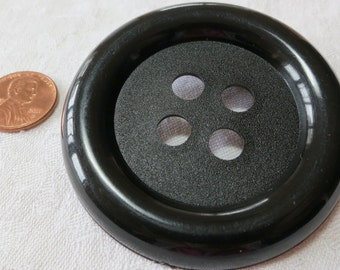 """Large 2.25"""" ins diameter, 4 hole, black plastic coat button. Rolled polished rim with pebble dash textured central well. HMFL14.10-11.29-1"""