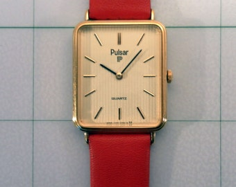 Vintage 1980's Pulsar 3 Jewel Quartz Watch,   Model Y100A Japan Mvt. Goldtone Dial, Holiday Red Leather Band. Running Condition.