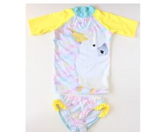 Girls Swimwear sublimated rash vest and bikini bottoms featuring sweet cockatoo print with yellow frill
