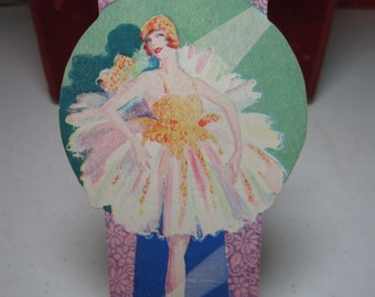 Pretty art deco die cut 1920's-30's bridge tally card shows a beautiful ballerina in a yellow and pink tutu with a spotlight on stage