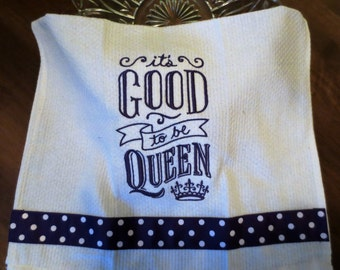 It's Good to Be Queen Machine Embroidery Kitchen Towel. White towel with purple embroidery and purple and white polka dot ribbon.