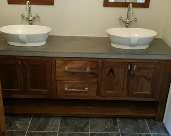 White walnut vanity with concrete top and vessel sinks.