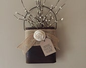 Tin wall pocket burlap ribbon accent with a cream rosette filled with paper grass cream berries home sweet home tag