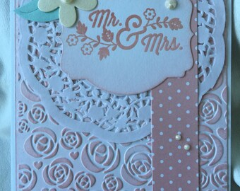 Pale pink wedding card with doily, flowers and bling