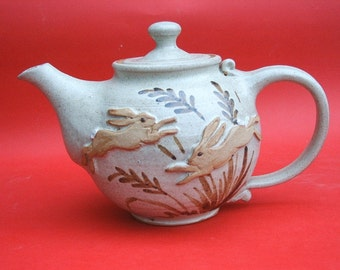Hand thrown and decorated stoneware pottery teapot with leaping hare design