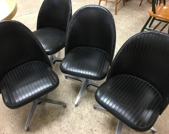 Black vinyl swivel chairs with Eames style bases