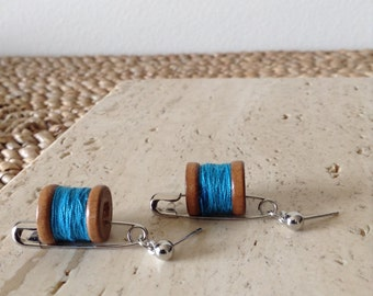Medium safety pin dangle stud earrings with wooden spool of deep teal thread. Hanging on by a string.