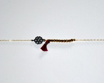 Gold-plated bracelet with micro Hematite, silk tassel and silver aged flower paved zircons