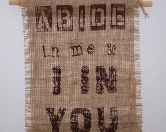 Scripture,  Bible Verse.  'Abide in me and I in You'.  John 15 v 4. KJV, AV version. Printed text in brown on stiffened Hessian Fabric.