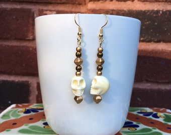 Cream skull and gold earrings