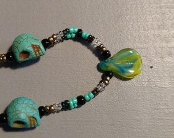 Turquoise skulls W/leaf glass bead