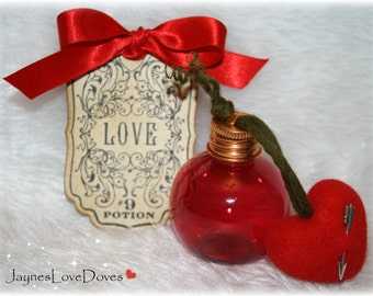 A shot through the heart by JaynesLoveDoves. Love Potion bottle with arrow pierced red felted heart.  Fill with your favourite tipple!