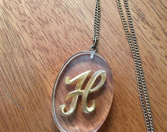 Gold Toned H in Clear Acrylic Necklace