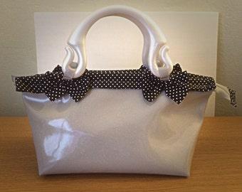 Pvc glitter handmade handbag with plastic handles. Black polka dot fabric lining with Pocket.