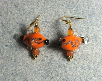 Orange and black lampwork fish bead earrings adorned with orange Czech glass beads.