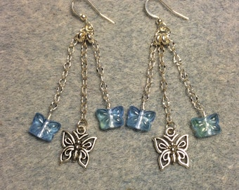 Silver butterfly charm dangle earrings attached to silver chain and adorned with small blue Czech glass butterfly beads.