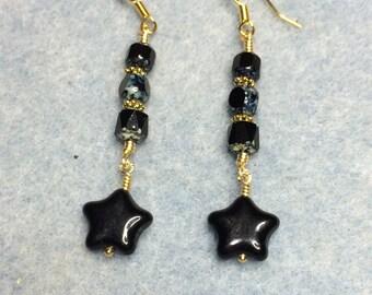 Black metallic star dangle earrings adorned with black Czech glass beads.