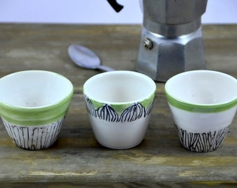 Three decorated ceramic cups set