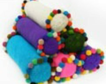 Cylindrical pillow with pompoms