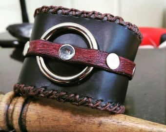 Rustic black leather cuff with border stitching and nickel ring