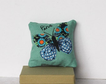 Pin cushion with butterfly appliqué in blue on turquoise linen