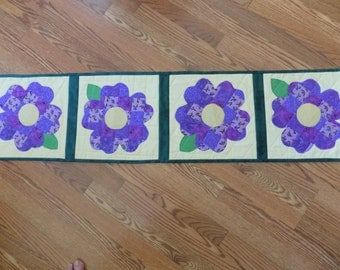 A table runner that has been pieced and quilted