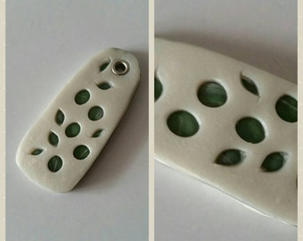 Polymer clay pendant, white with green background, leaf pattern