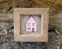 Framed clay house wall art, pale pink in a limed wooden frame.