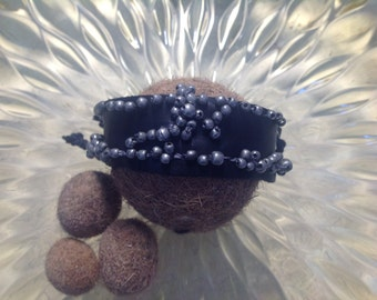 Black leather strap and metal beads