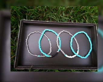 4 piece seed bead set. Blue, clear, white and black beaded bracelet set