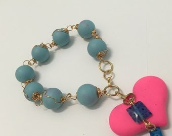 Stretchy, sky blue with pink, with blue pink and hanging heart pendant.