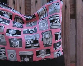 Pink shoulder bag with Polaroids and vintage cameras