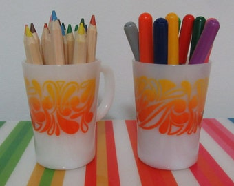 Two funky 1970s Pyrex mugs with yellow and orange design