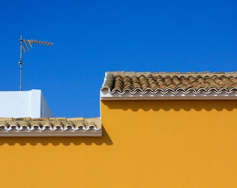 Mediterranean ochre wall and traditional rooftop tiles with brilliant blue sky, Oliva, Valencia, Spain