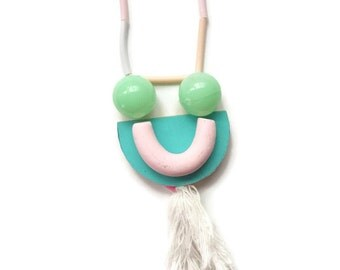 pastel U shape polymer clay necklace with plastic bauble and cotton tassel