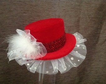 Red velvet mini top hat fascinator, with white netting and feathers.