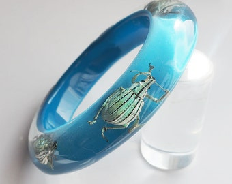 Deep blue lucite bracelet with five iridescent real insects
