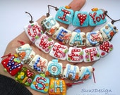 Handmade lampwork block letter beads made by Suuz sra