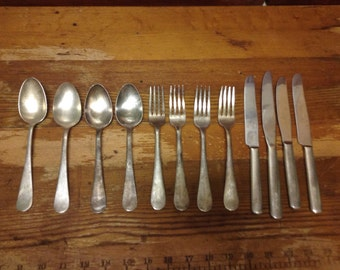 """Four sets of knives, forks, and spoons marked """"Woolworth"""""""
