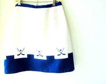"Golf vintage 70s white , ""waffle"", thick polyester , mini Q- skirt with  navy blue applique. Made by Leon Levin. Size Small."