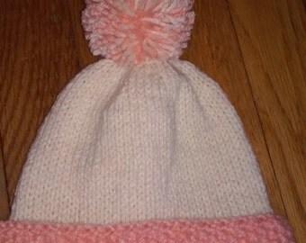 Hand Knitted infant Aran, offwhite, Cream and peach Hat,  Cuff worked in garter stitch  with pompom, fits newborn to 3 month