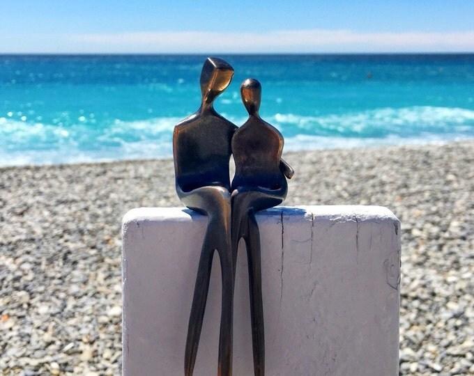 Caress: My favorite bronze sculpture, he has his arm around her, they elegantly cross their legs creating elegant art