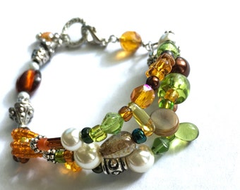 Multi strand bracelet - green, orange, and brown crystals and pearls